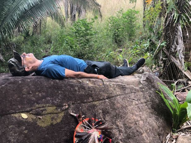 Mauricio lies on the carved boulder